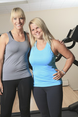 Portrait of two young women smiling in a bright exercise room