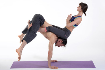 Practicing acro yoga exercises in group on white background.