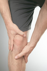 Man with both palm around knee cap to show pain and injury on kn
