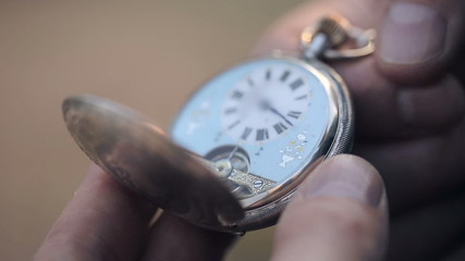 A man looks at the time of old pocket watches and closes them.