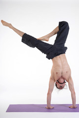 An attractive athletic man doing a yoga pose in studio.