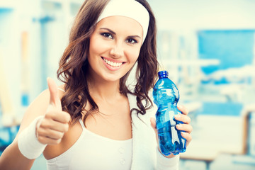Woman with bottle of water, at fitness gym