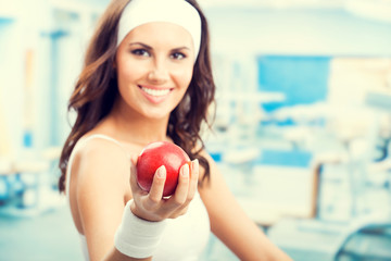 Woman with apple, at fitness gym