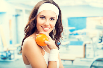 Woman with orange, at fitness gym