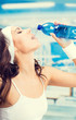 Woman drinking water, at fitness gym