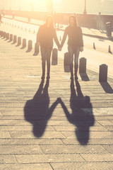 Shadows of Female Twins Holding Hands in the City.