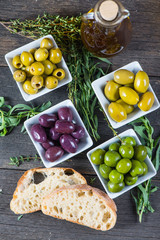 Selection of fresh olives with herbs and oil from above