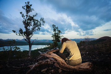 Sad young woman sitting on burned hill