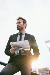 Businessman Holding a Newspaper in a Finance Area