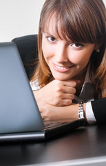 Cheerful young businesswoman with laptop