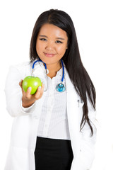 Young female doctor offering a green apple