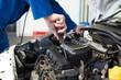 Mechanic using screwdriver on engine