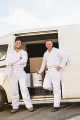Painters smiling leaning against their van
