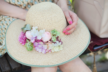 Straw hat with flowers in hands of young girl