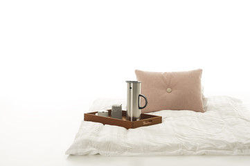 Tray with hot coffee on a soft down comforter