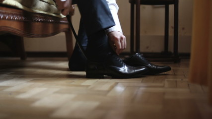 The man puts shoes on. HD shot with slider