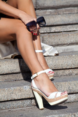 Legs of beautiful girl in high heels sitting on the steps