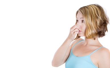 Portrait young woman pinches her nose very bad smell