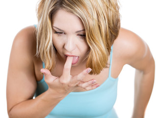 Young woman sticking her finger in throat about to throw up