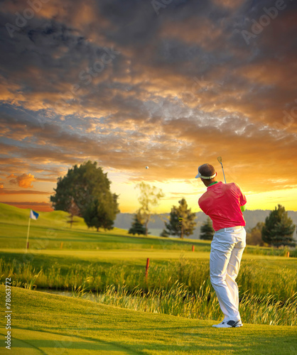 Tuinposter Golf Man playing golf against colorful sunset
