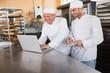 Leinwanddruck Bild - Smiling bakers working together on laptop