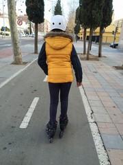 mujer joven patinando por la ciudad con casco