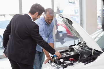 Two men looking at a car engine