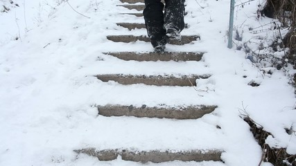 Man falling down the broken stairs covered with snow