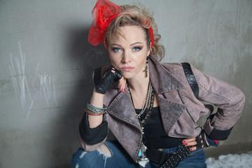 Beautiful blonde woman in rock style posing on the street