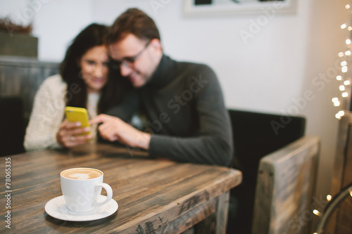 Young couple in cafe sitting with smartphone and Young couple in