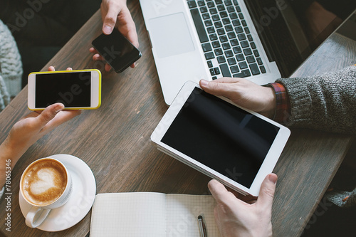 Hands with smartphones, tablet over table with laptop and coffee - 78065346
