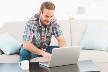 Smiling man at home on a laptop