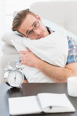 Bored man beside alarm clock
