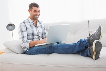 Relaxing man on a sofa with a laptop