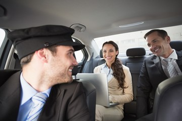 Handsome chauffeur smiling at clients