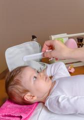 Hand of mother combing her baby lying