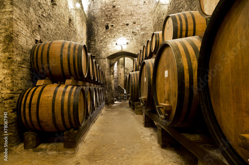 Poster Wine barrels stacked in the old cellar of the winery