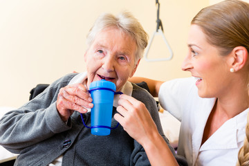 Pflegerin gibt alter Frau Tee zum Trinken im Seniorenheim
