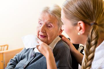 Altenpflegerin wischt alter Frau den Mund ab