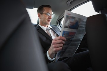 Focused businessman reading the newspaper