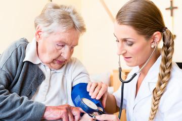 Pflegerin misst Blutdruck bei Senior Patientin