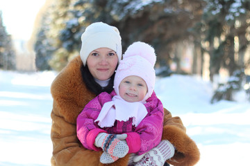 Mother and daughter in winter smiling happy family in the park