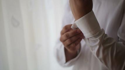 The man wears white shirt and cufflinks