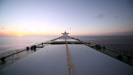 Bulk carrier ship underway at sunset