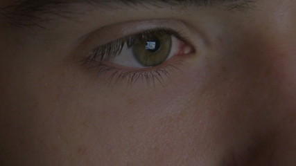 4k UHD - Close-up of a young man eyes browsing on a tablet pc