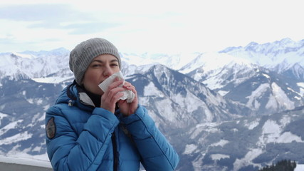 Young woman sneezes in winter mountains