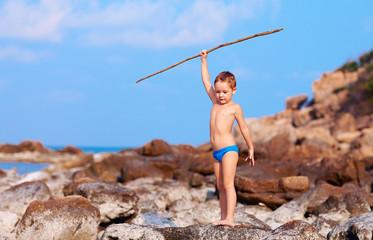 boy with spear pretends like he is aborigine on desert island