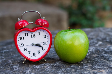 red clock and apple