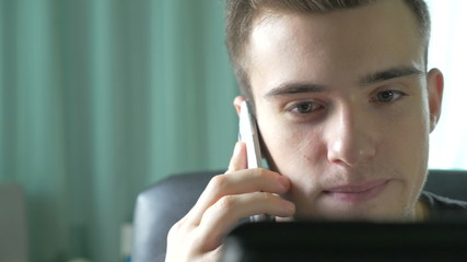 4k UHD - Young man browsing on a tablet pc and talking