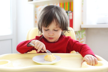2 years boy in red shirt eating omelette